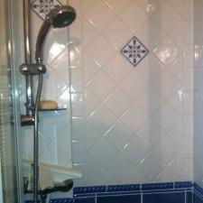 Salle de bains provençale réalisée dans le var avec coin cabine de douche, lavabo sur bâti recouvert de carreaux, sèche-serviette.